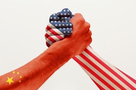 Guerra commerciale e rivalità. Due mani maschili in competizione nel braccio di ferro colorato in bandiere di Cina e America isolate su sfondo bianco per studio. Concetto di relazioni economiche e politiche, embargo. Archivio Fotografico