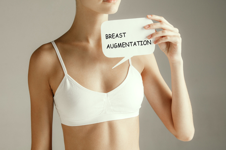 Zdrowie kobiety. Modelka trzyma kartę z napisem powiększanie piersi. Młoda dorosła dziewczyna z papieru na znak lub symbol na białym tle na szarym tle studio. Problem medyczny i rozwiązanie.