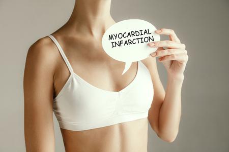Mujer que sufre un infarto. Salud de la mujer. Modelo femenino que sostiene la tarjeta con palabras infarto de miocardio cerca de la mama. Problema y solución médica. Foto de archivo