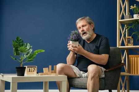 Essayer de trouver le bonheur. Le vieil homme barbu atteint de la maladie d'Alzheimer a des problèmes de motricité des mains. Concept de maladie, perte de mémoire due à la démence, soins de santé, troubles neurologiques, tristesse.