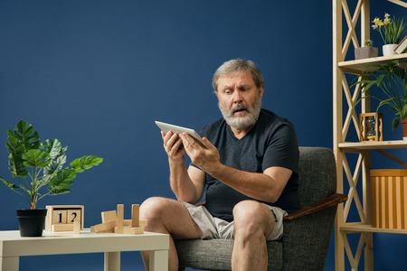 No entiende el mundo. Anciano barbudo con enfermedad de alzheimer tiene problemas con la motricidad de sus manos. Enfermedad, pérdida de memoria debido a demencia, salud, trastorno neurológico, concepto de tristeza.