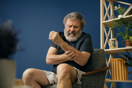 Injustice. Old bearded man sitting on the chair and suffering from pain in arm muscles on blue background. Concept of illness, diseases of the joints and bones, surgical pathology, healthcare.