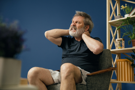 Lifes getting hard. Old bearded man sitting on the chair and suffering from neck pain on blue background. Concept of illness, diseases of the joints and bones, surgical pathology, healthcare.
