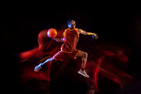 See the target. African-american young basketball player of red team in action and neon lights over dark studio background. Concept of sport, movement, energy and dynamic, healthy lifestyle. 스톡 콘텐츠