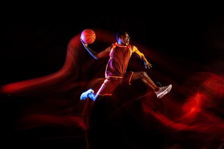 Emociones de ganador. Joven jugador de baloncesto afroamericano del equipo rojo en acción y luces de neón sobre fondo oscuro de estudio. Concepto de deporte, movimiento, energía y estilo de vida dinámico y saludable.