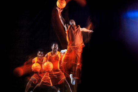 Higher than sky. African-american young basketball player of red team in action and neon lights over dark studio background. Concept of sport, movement, energy and dynamic, healthy lifestyle.