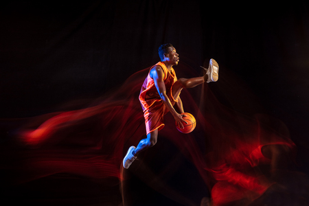 Higher and stronger. African-american young basketball player of red team in action and neon lights over dark studio background. Concept of sport, movement, energy and dynamic, healthy lifestyle.