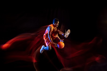 Slam dunk. African-american young basketball player of red team in action and neon lights over dark studio background. Concept of sport, movement, energy and dynamic, healthy lifestyle.