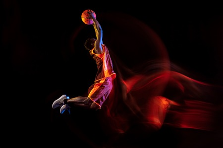 Catching the sun. African-american young basketball player of red team in action and neon lights over dark studio background. Concept of sport, movement, energy and dynamic, healthy lifestyle.