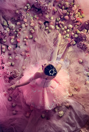 Smell of roses.Top view of beautiful young woman in pink ballet tutu surrounded by flowers. Spring mood and tenderness in coral light. Art photo. Concept of spring, blossom and natures awakening.