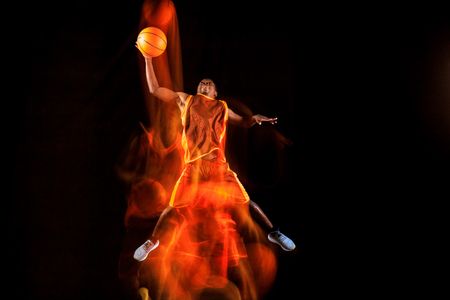 Play in fire. African-american young basketball player of red team in action and neon lights over dark studio background. Concept of sport, movement, energy and dynamic, healthy lifestyle.