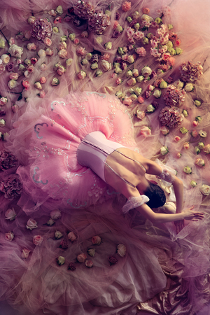 Sleepless night. Top view of beautiful young woman in pink ballet tutu surrounded by flowers. Spring mood and tenderness in coral light. Art photo. Concept of spring, blossom and natures awakening. 写真素材