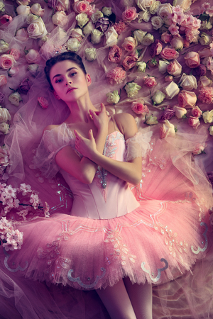 Appeasement. Top view of beautiful young woman in pink ballet tutu surrounded by flowers. Spring mood and tenderness in coral light. Art photo. Concept of spring, blossom and natures awakening. Stock Photo