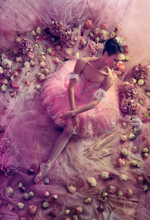 Perfect pink. Top view of beautiful young woman in pink ballet tutu surrounded by flowers. Spring mood and tenderness in coral light. Art photo. Concept of spring, blossom and natures awakening.