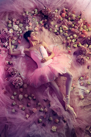 Sweet dreams. Top view of beautiful young woman in pink ballet tutu surrounded by flowers. Spring mood and tenderness in coral light. Art photo. Concept of spring, blossom and natures awakening.
