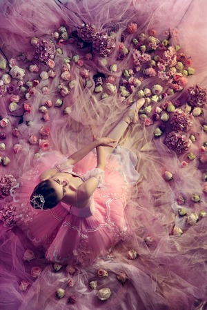 Looking for feelings. Top view of beautiful young woman in pink ballet tutu surrounded by flowers. Spring mood and tenderness in coral light. Art photo. Concept of spring, blossom, natures awakening.