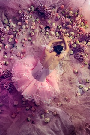 All the beauty around. Top view of beautiful young woman in pink ballet tutu surrounded by flowers. Spring mood and tenderness in coral light. Art photo. Concept of spring, blossom, natures awakening.