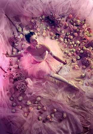 Weightless. Top view of beautiful young woman in pink ballet tutu surrounded by flowers. Spring mood and tenderness in coral light. Art photo. Concept of spring, blossom and natures awakening. Stock fotó