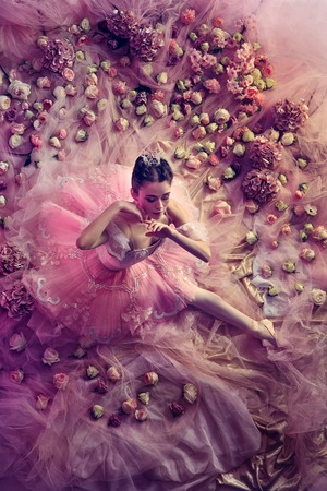 Embarrassment. Top view of beautiful young woman in pink ballet tutu surrounded by flowers. Spring mood and tenderness in coral light. Art photo. Concept of spring, blossom and natures awakening.