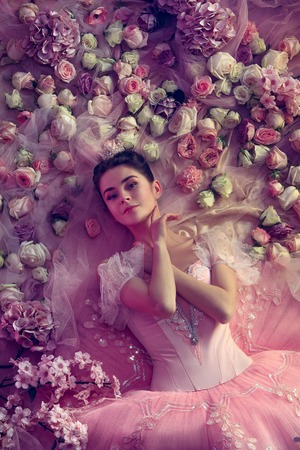 Keep loving. Top view of beautiful young woman in pink ballet tutu surrounded by flowers. Spring mood and tenderness in coral light. Art photo. Concept of spring, blossom and natures awakening. Banque d'images