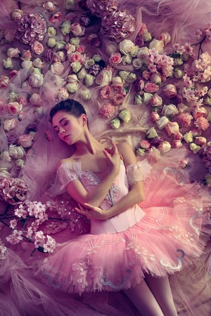 Touch of sunset. Top view of beautiful young woman in pink ballet tutu surrounded by flowers. Spring mood and tenderness in coral light. Art photo. Concept of spring, blossom and natures awakening.