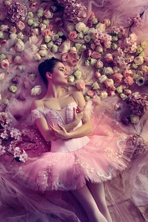 Light melancholy. Top view of beautiful young woman in pink ballet tutu surrounded by flowers. Spring mood and tenderness in coral light. Art photo. Concept of spring, blossom and natures awakening.