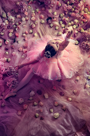 Looking higher. Top view of beautiful young woman in pink ballet tutu surrounded by flowers. Spring mood and tenderness in coral light. Art photo. Concept of spring, blossom and natures awakening.