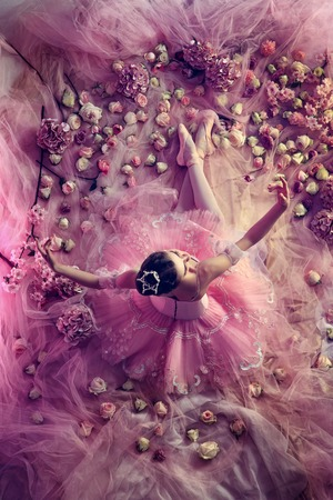 Looking for emotions. Top view of beautiful young woman in pink ballet tutu surrounded by flowers. Spring mood and tenderness in coral light. Art photo. Concept of spring, blossom, natures awakening.