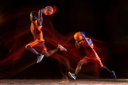 Two steps for winning. African-american young basketball player of red team in action and neon lights over dark studio background. Concept of sport, movement, energy and dynamic, healthy lifestyle.