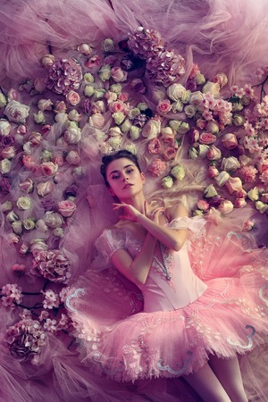 Basking in the sunset. Top view of beautiful young woman in pink ballet tutu surrounded by flowers. Spring mood and tenderness in coral light. Art photo. Concept of spring, blossom, natures awakening. Stock Photo