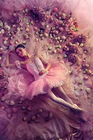 Feeling weightless. Top view of beautiful young woman in pink ballet tutu surrounded by flowers. Spring mood and tenderness in coral light. Art photo. Concept of spring, blossom and natures awakening.