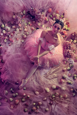 Perfect look. Top view of beautiful young woman in pink ballet tutu surrounded by flowers. Spring mood and tenderness in coral light. Art photo. Concept of spring, blossom and natures awakening. Stock fotó