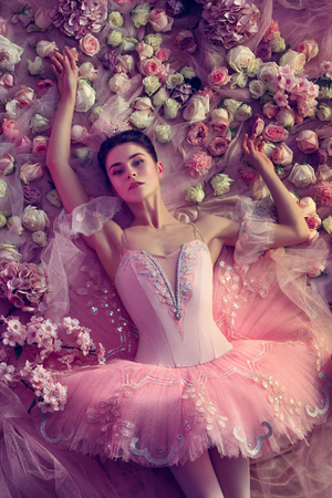 Deep eyes. Top view of beautiful young woman in pink ballet tutu surrounded by flowers. Spring mood and tenderness in coral light. Art photo. Concept of spring, blossom and natures awakening. Stock Photo - 120928510