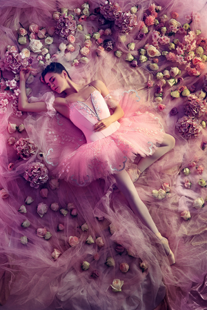 Graceful youth. Top view of beautiful young woman in pink ballet tutu surrounded by flowers. Spring mood and tenderness in coral light. Art photo. Concept of spring, blossom and natures awakening.