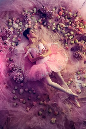 Light as a petal. Top view of beautiful young woman in pink ballet tutu surrounded by flowers. Spring mood and tenderness in coral light. Art photo. Concept of spring, blossom and natures awakening.