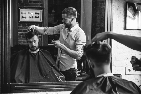 Young handsome barber making haircut for attractive bearded man at barbershop. Black and white or colorless photo. Hairstyle, salon, hairdresser, barber shop, lifestyle concept. Caucasian male models. 免版税图像