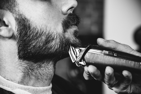 Young handsome barber making haircut for attractive bearded man at barbershop. Black and white or colorless photo. Hairstyle, salon, hairdresser, barber shop, lifestyle concept. Caucasian male models.
