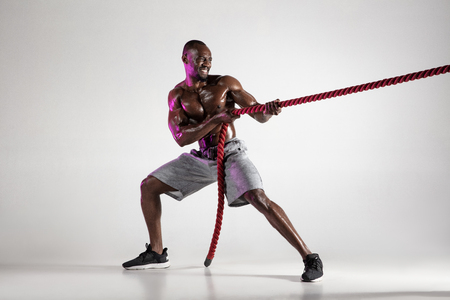 Defend your opinion. Young african-american bodybuilder training on grey studio background. Muscular single male model in sportwear with battle rope. Concept of sport, bodybuilding, healthy lifestyle.