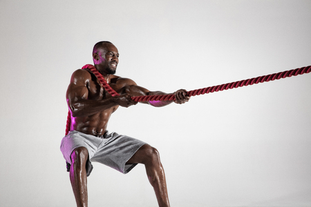 When dreams so close. Young african-american bodybuilder training on grey background. Muscular male model in sportwear pulling the battle rope. Concept of sport, bodybuilding, healthy lifestyle.