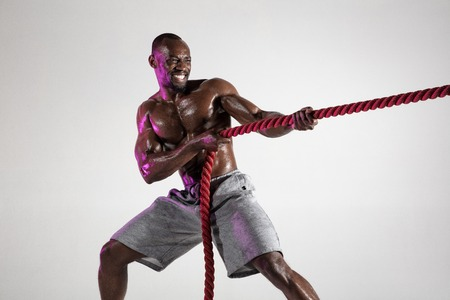Overcoming. Young african-american bodybuilder training over grey background. Muscular single male model in sportwear pulling the battle rope. Concept of sport, bodybuilding, healthy lifestyle.
