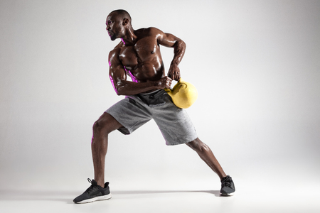 Poise in his choice. Young african-american bodybuilder training over grey studio background. Muscular single male model in sportwear with the weight. Concept of sport, bodybuilding, healthy lifestyle.