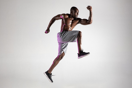 Run for adventures. Young african-american bodybuilder training over grey studio background. Muscular single male model jumping in sportwear. Concept of sport, bodybuilding, healthy lifestyle. Banco de Imagens