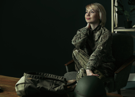 Dreaming about home and family, happy to come back. Portrait of young female soldier. Woman in military uniform during meeting with psychotherapist for psychological rehabilitation and PTSD treatment. Stock Photo