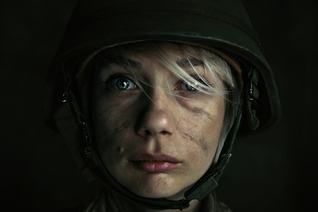 Only one chance to be alive. Close up portrait of young female soldier. Woman in military uniform on the war. Depressed and having problems with mental health and emotions, PTSD. Standard-Bild