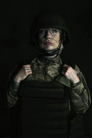 Looking for brightness and colors in grey world. Close up portrait of young female soldier. Woman in military uniform on the war. Depressed, having problems with mental health and emotions, PTSD.