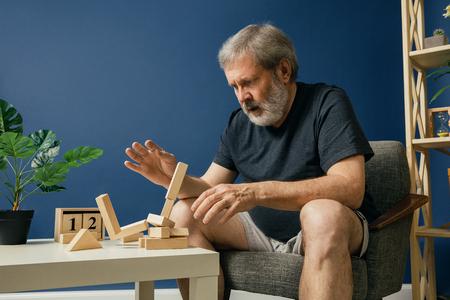 Intentando detener lo irreversible. Anciano barbudo con enfermedad de alzheimer tiene problemas con la motricidad de sus manos. Enfermedad, pérdida de memoria debido a demencia, salud, trastorno neurológico, concepto de tristeza.