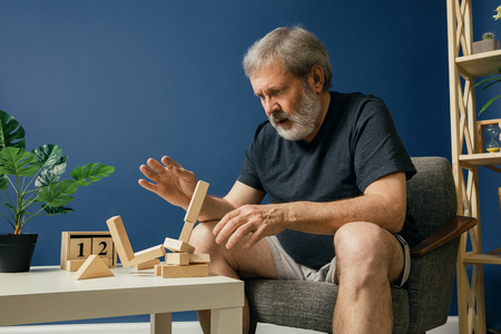 Trying stop the irreversible. Old bearded man with alzheimer desease has problems with his hands motor skills. Illness, memory loss due to dementia, healthcare, neurological disorder, sadness concept.
