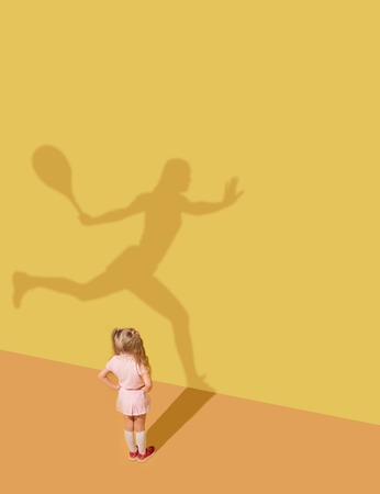 Faster and stronger than others. Childhood and dream concept. Conceptual image with child and shadow on the yellow studio wall. Little girl want to become tennis player, champion, winner, sportswoman. Stock Photo