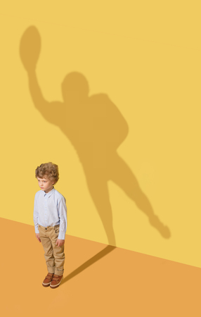 Best member of the team. Childhood and dream concept. Conceptual image with child and shadow on the yellow studio wall. Little boy want to become american football player and to build a sport career.