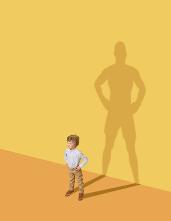 I could protect my family. Future champion. Childhood and dream concept. Conceptual image with child and shadow on the yellow studio wall. Little boy want to become a boxer and to build a sport career. 免版税图像